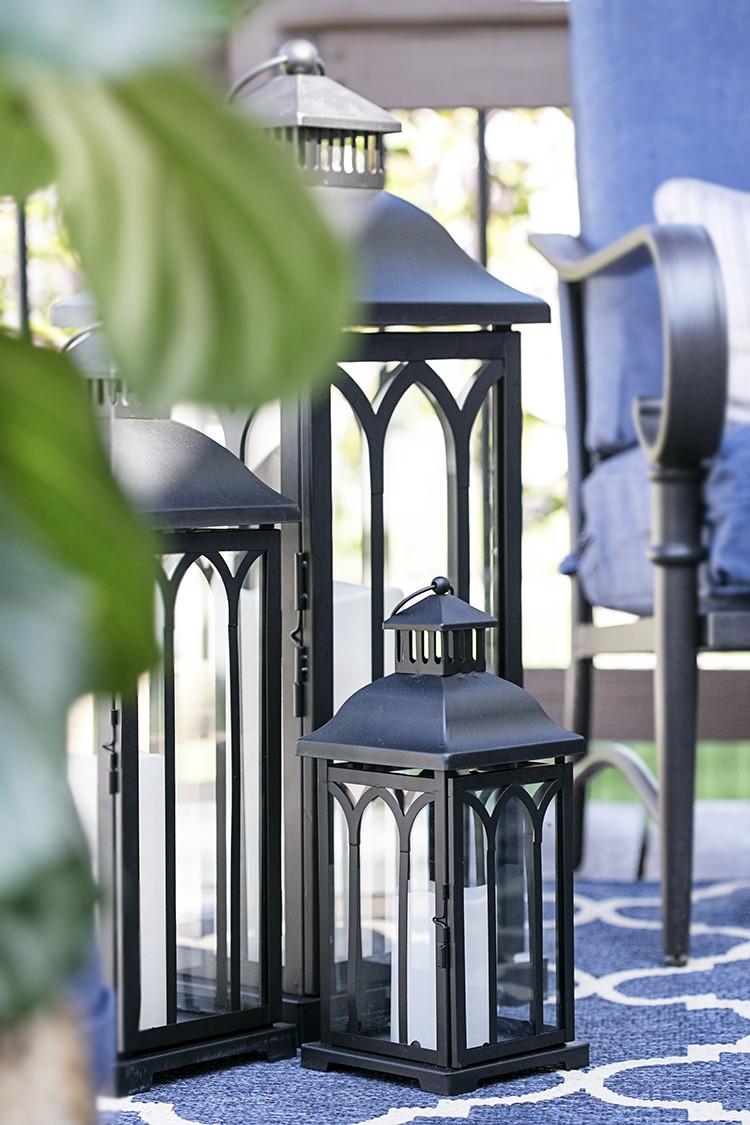 Black metal lanterns on a deck with a blue color scheme