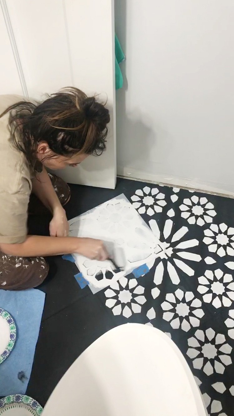 Painting a stencil design on a bathroom floor